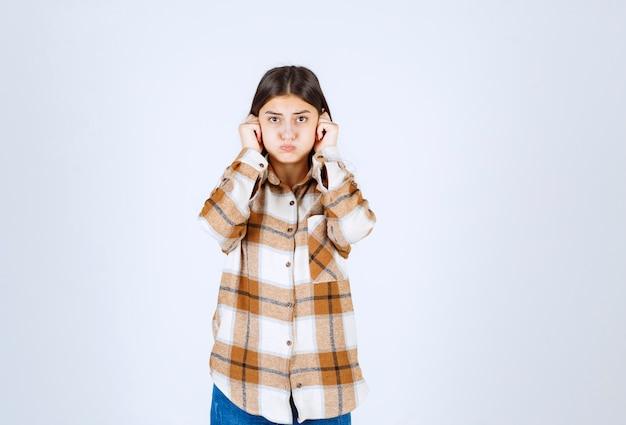 Porträt der jungen frau, die mit traurigem ausdruck auf weißer wand steht.