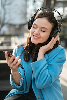 Porträt der jungen frau, die musik draußen genießt