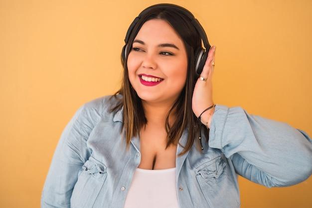Porträt der jungen frau, die musik mit kopfhörern draußen gegen gelbe wand hört