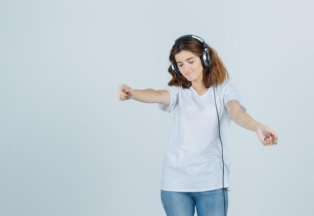 Porträt der jungen frau, die musik mit kopfhörern im weißen t-shirt, in den jeans und in der verspielten vorderansicht genießt