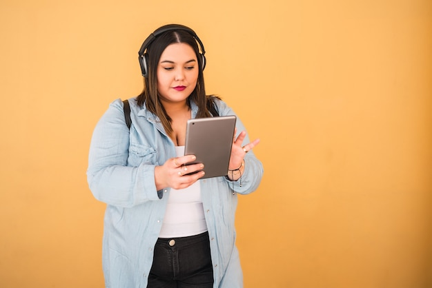 Porträt der jungen frau, die musik mit kopfhörern und digitalem tablett draußen gegen gelbe wand hört