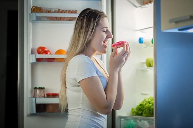 Porträt der jungen frau, die nachts donut aus dem kühlschrank nimmt. konzept der ungesunden ernährung