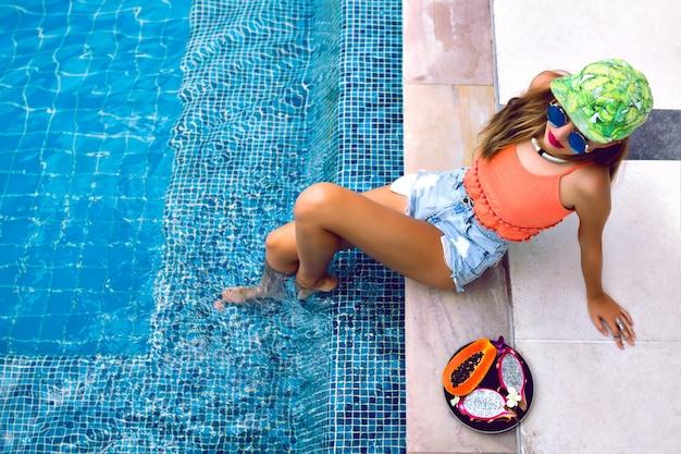 Porträt der jungen frau, die nahe pool mit tropischen früchten aufwirft