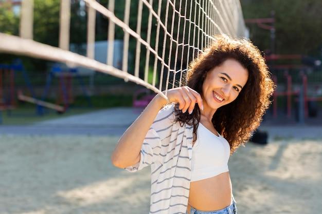 Porträt der jungen frau, die neben einem volleyballfeld mit kopienraum aufwirft