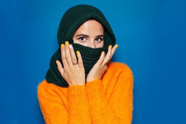Porträt der jungen frau, die orangefarbenen pullover und grünen schal trägt