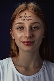 Porträt der jungen frau, die psychische gesundheitsprobleme überwindet. tätowierung auf der stirn ich bin selbst zerstört - wurde wiedergeboren.