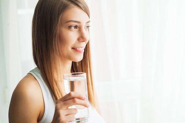 Porträt der jungen frau, die reines wasser aus glas erfrischend trinkt.