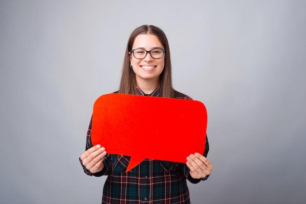 Porträt der jungen frau, die rote sprechblase mit copyspace hält