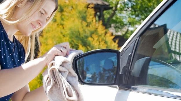 Porträt der jungen frau, die rückspiegel ihres autos säubert.