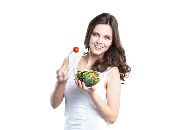 Porträt der jungen frau, die salat lokalisiert isst. ernährungskonzept und gesunder lebensstil.