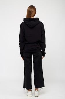Porträt der jungen frau, die schwarzen kapuzenpulli trägt, isoliertes studiobild auf weißem hintergrund