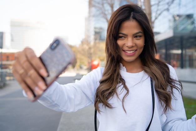 Porträt der jungen frau, die selfies mit ihrem mophilen telefon nimmt, während sie draußen steht