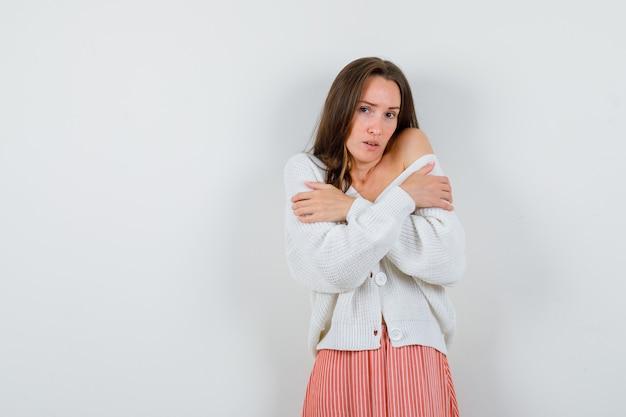 Porträt der jungen frau, die sich umarmt oder sich kalt in der strickjacke isoliert fühlt