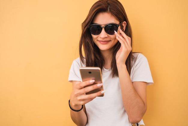 Porträt der jungen frau, die sommerkleidung trägt und ihr handy gegen gelben hintergrund benutzt. stadt- und kommunikationskonzept.