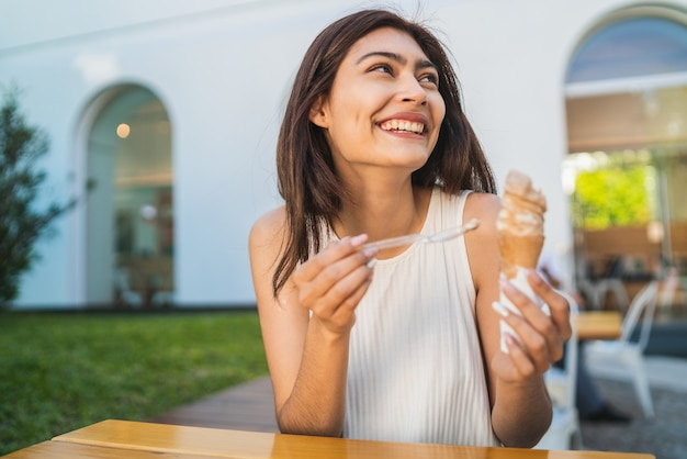 Porträt der jungen frau, die sonniges wetter genießt, während sie ein eis draußen isst