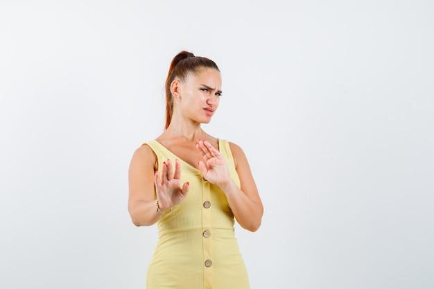 Porträt der jungen frau, die stoppgeste im gelben kleid zeigt und angewiderte vorderansicht schaut