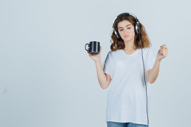 Porträt der jungen frau, die tasse des getränks im weißen t-shirt hält und verträumte vorderansicht schaut