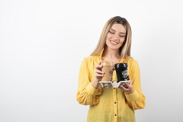 Porträt der jungen frau, die tassen des kaffees auf weißem hintergrund betrachtet.