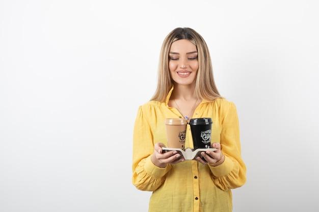 Porträt der jungen frau, die tassen des kaffees beim lächeln hält.