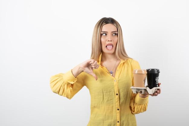 Porträt der jungen frau, die tassen kaffee hält und daumen nach unten gibt.