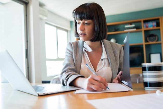 Porträt der jungen frau, die von zu hause mit laptop und akten arbeitet. home-office-konzept. neuer normaler lebensstil.