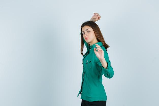 Porträt der jungen frau, die vorgibt, etwas im grünen hemd wegzuwerfen und ernst zu schauen