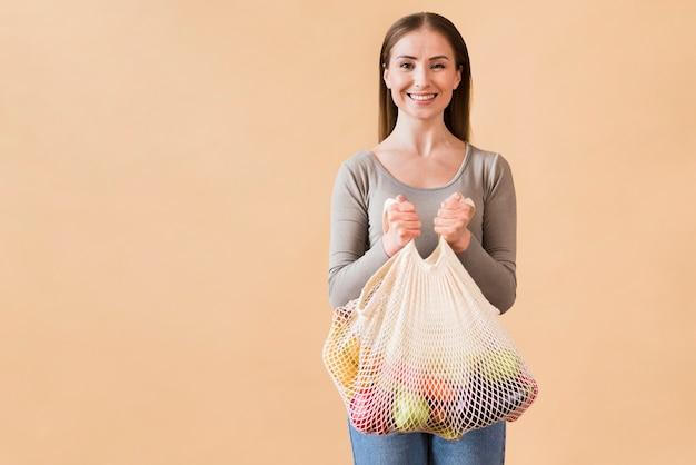 Porträt der jungen frau, die wiederverwendbaren beutel mit lebensmitteln hält