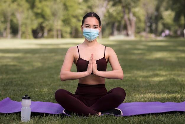 Porträt der jungen frau, die yoga im freien ausübt