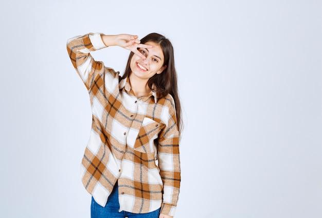 Porträt der jungen frau, die zur kamera über weißer wand steht und lächelt.