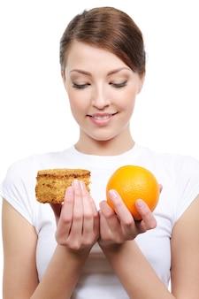Porträt der jungen frau, die zwischen kuchen und orange wählt