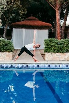 Porträt der jungen frau (eignung, yoga, gesunder körper) am swimmingpool