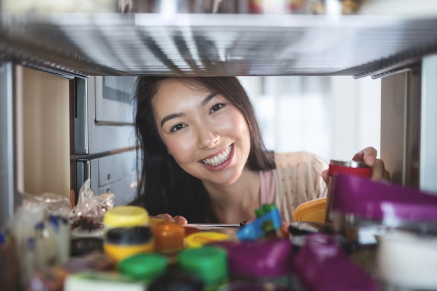 Porträt der jungen frau eine flasche vom speicherkabinett auswählend