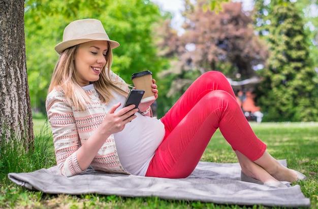 Porträt der jungen frau glücklich auf gras halten handy und kaffee zu gehen. ganzkörper-porträt der glücklichen frau liegt im gras sms mit smartphone