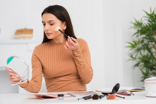 Porträt der jungen frau ihr make-up tuend