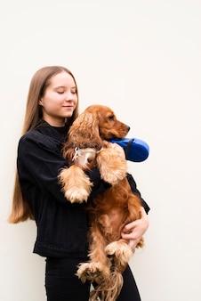 Porträt der jungen frau ihren hund umarmend