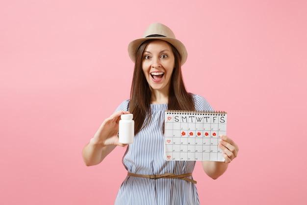 Porträt der jungen frau im blauen kleid, das weiße flasche mit pillen hält, kalender der weiblichen perioden, menstruationstage einzeln auf hintergrund überprüfend. gynäkologisches konzept des medizinischen gesundheitswesens. platz kopieren.
