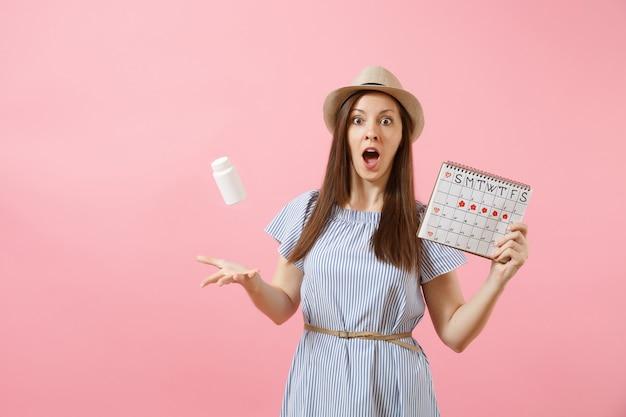 Porträt der jungen frau im blauen kleid werfen weiße flasche mit pillen, kalender der weiblichen perioden hoch und überprüfen die menstruationstage einzeln auf hintergrund. gynäkologisches konzept des medizinischen gesundheitswesens. platz kopieren
