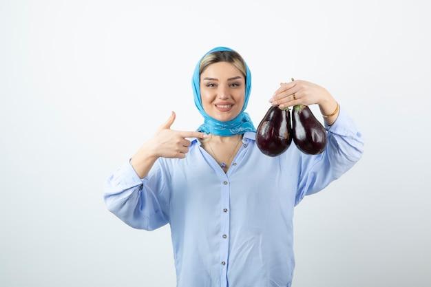 Porträt der jungen frau im blauen schal, der auf ungekochte auberginen zeigt