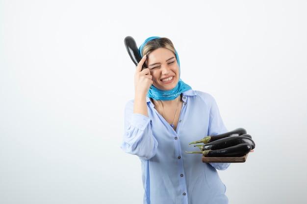 Porträt der jungen frau im blauen schal, der holzbrett der ungekochten auberginen hält
