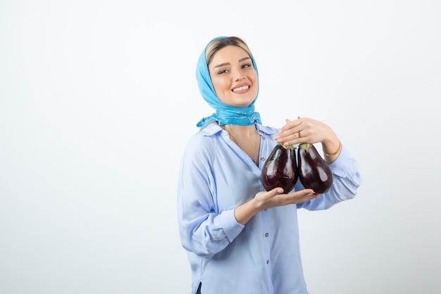 Porträt der jungen frau im blauen schal, der ungekochte auberginen hält