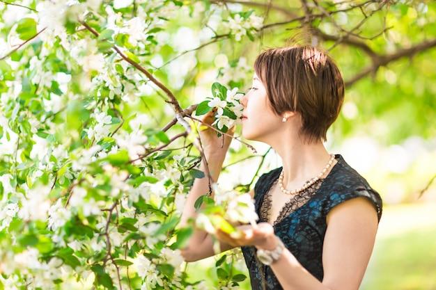 Porträt der jungen frau im blumengarten. frühlingsmandelblüten blühen.