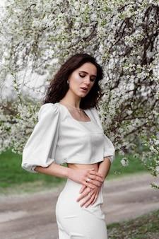 Porträt der jungen frau im garten. attraktives mädchen trug weißes kleid, das nahe blühenden bäumen aufwirft.