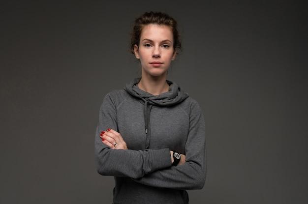 Porträt der jungen frau im grauen hoodie gegen düsteres lokalisiert
