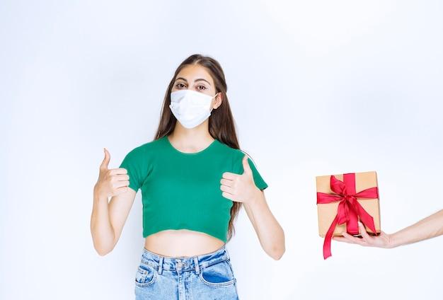 Porträt der jungen frau im grünen hemd, das daumen nahe der geschenkbox aufgibt.