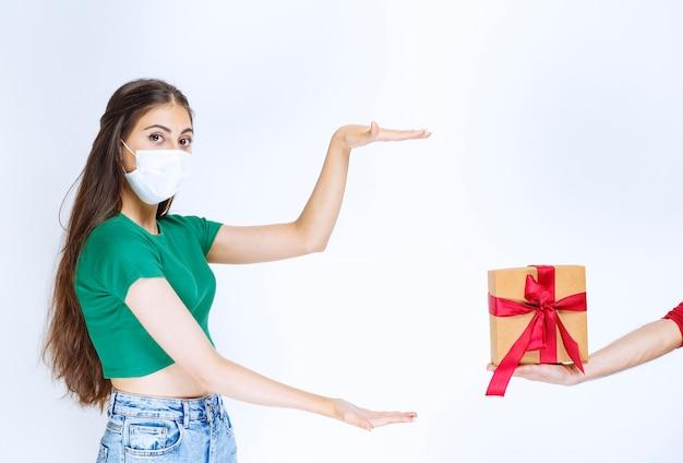 Porträt der jungen frau im grünen hemd, das geschenkbox zeigt.