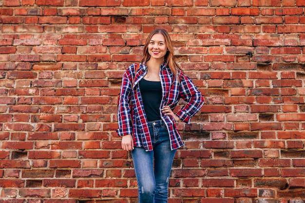 Porträt der jungen frau im karierten hemd und in den blauen jeans, die gegen die rote backsteinmauer stehen