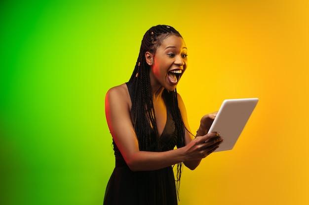 Porträt der jungen frau im neonlicht auf gradientenhintergrund. halten sie eine tablette.