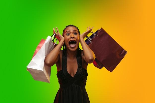 Porträt der jungen frau im neonlicht mit einkaufstüten, schwarzer freitag