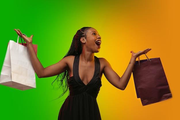 Porträt der jungen frau im neonlicht mit einkaufstüten