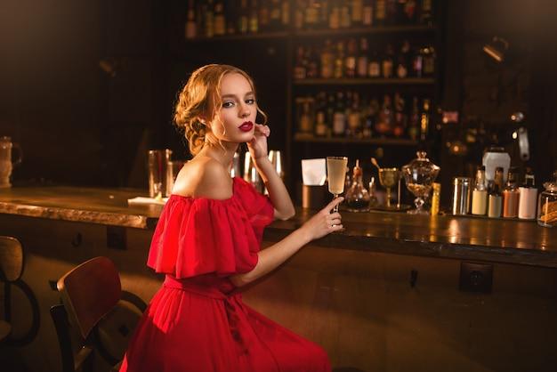 Porträt der jungen frau im roten kleid, das an der bartheke sitzt. schöne dame mit cocktail in der hand im club